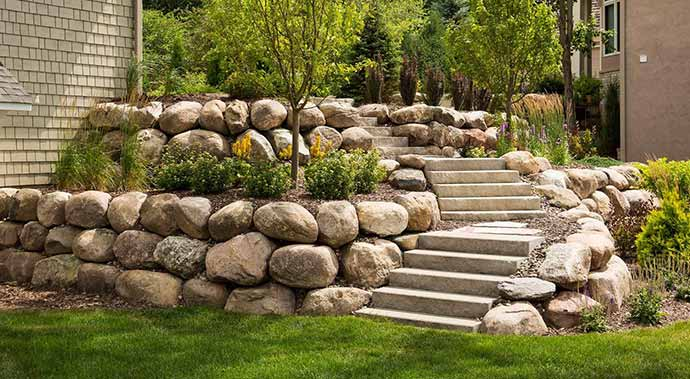 Two level stone retaining wall with stone steps.